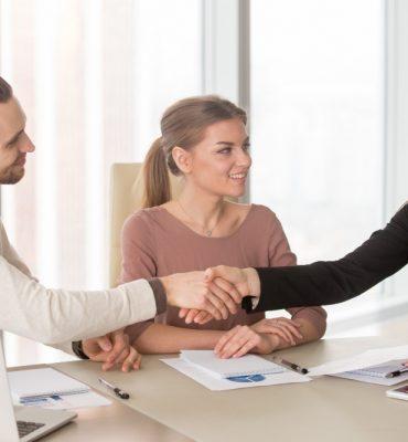 businessman-businesswoman-handshaking-business-meeting-sitting-office